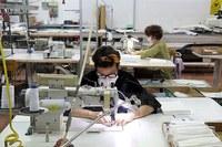 Coronavirus, lavoratrice che cuce, mascherine, fabbrica