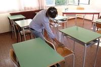 Coronavirus, bidella che pulisce i banchi, aula, mascherina, igienizzazione